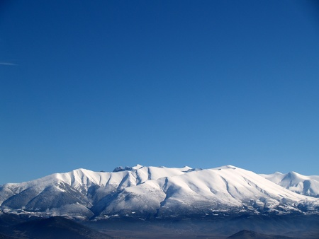 olympus: Olympus Mountain covered by snow and a blue sky in Greece