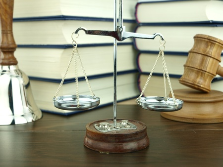 legal scales: Scale of justice, hand bell and judge�s gavel with a stack of legal books background