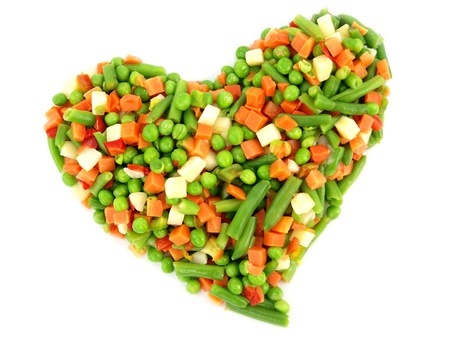 Heart of a frozen mixed vegetables isolated on white background photo