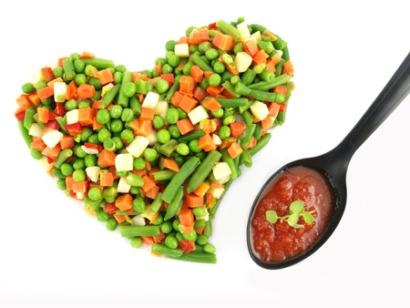 sause: Heart of a frozen mixed vegetables with tomato souse in spoon