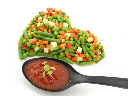 Heart of a frozen mixed vegetables with tomato souse in spoon photo