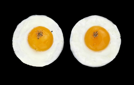 huevos fritos:  Dos huevos fritos como ojos en una pan negra  Foto de archivo