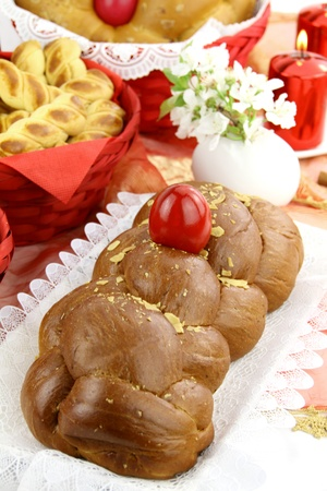 easter cookie: A traditional sweet brioche bread, called tsoureki, decorated with red eggs (Greek recipe)  Stock Photo