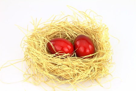 consuetude: Red eastern eggs in the nest over white background  Stock Photo