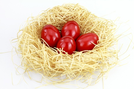 consuetude: Red easter eggs in the nest over white background  Stock Photo