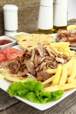 gyros: Plate of traditional Greek gyros or Turkish kebab with meat, fried potatoes, tomato and onion Stock Photo