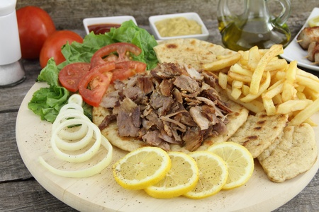 gyros: Plate of traditional Greek gyros with meat, fried potatoes, tomato and onion