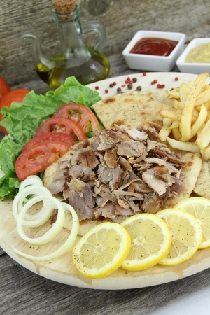Plate of traditional Greek gyros or Turkish kebab with meat, fried potatoes, tomato and onion photo