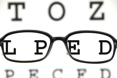 refractive: Black spectacles on an eye chart