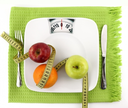 weight: Diet concept. Fruits with measuring tape on a plate like weight scale
