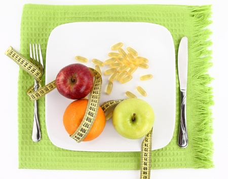 Diet concept. Fruits and vitamins with measuring tape on a plate  photo