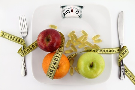 Diet concept. Fruits and vitamins with measuring tape on a plate like weight scale  photo