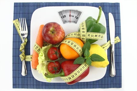 weight: Fruits and vegetables with measuring tape on a plate as weight scale