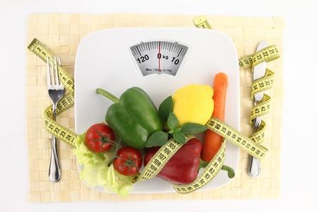 cinta metrica: Verduras con cinta en un plato como escala de peso de medici�n  Foto de archivo