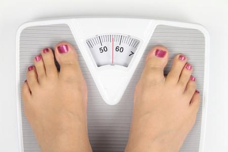 girl feet: Woman� s feet on bathroom scale Stock Photo