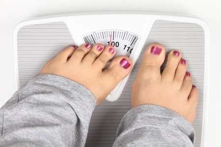 obese girl: Woman' s feet on bathroom scale Stock Photo