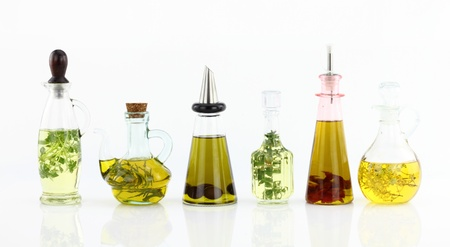 Various bottles of olive oil with herbs inside photo