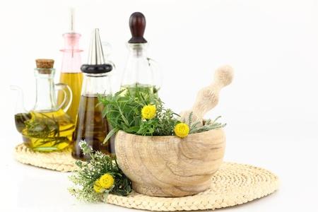 aceite de cocina: Mortero con las hierbas y las botellas de aceite de oliva Foto de archivo