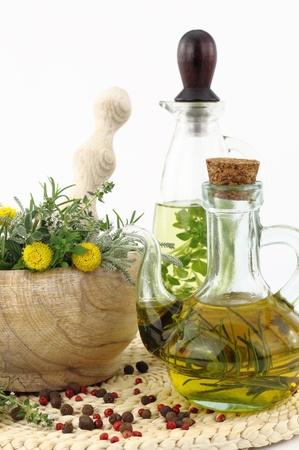 tomillo: Mortero con las hierbas y las botellas de aceite de oliva Foto de archivo