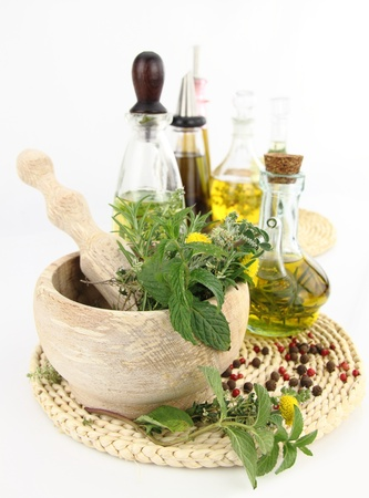 salad dressing: Mortar and pestle with herbs and bottles of olive oil