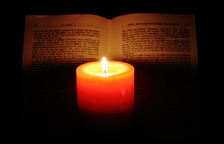 Candle and book on dark background photo