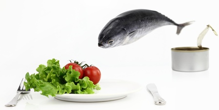 canned meat: Tuna fish jumping out of the can into the plate