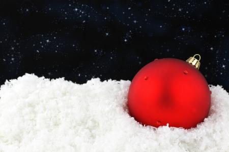 Red Christmas ball on snow  photo