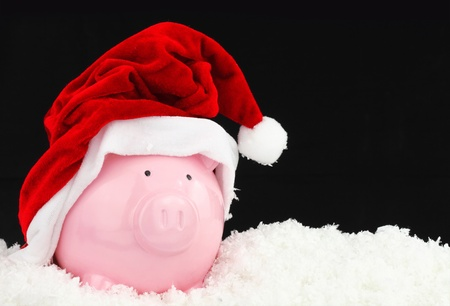 christmas savings: Santa Claus piggy bank on snow