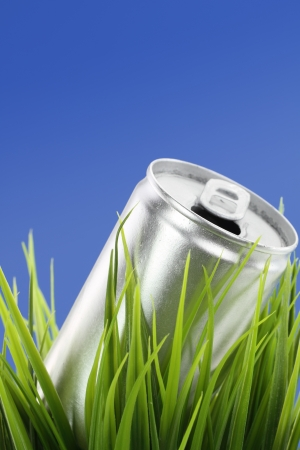 Recycle concept. Drink can on green grass photo