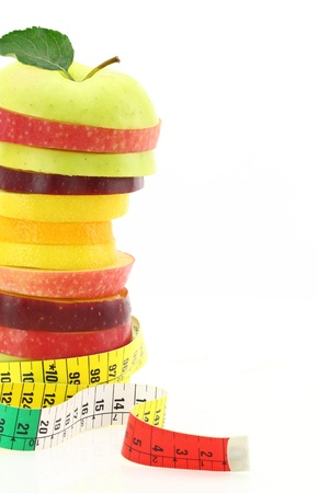 Diet concept. Fruits with measuring tape photo