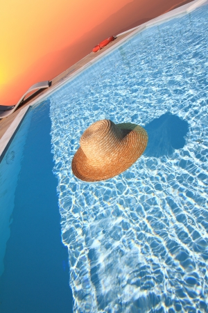 Straw hat in the pool. End of summer concept photo