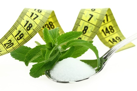 Fresh Stevia Rebaudiana, sugar in a spoon and measuring tape photo