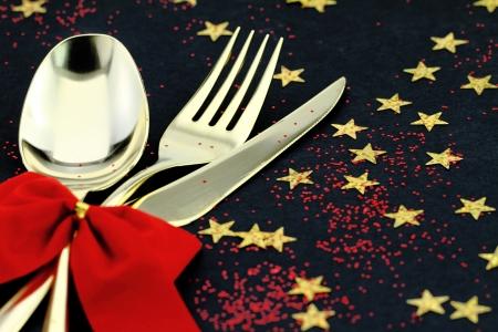 cena de navidad: Navidad cubiertos. Cuchara, tenedor y cuchillo apilados sobre un fondo estrellado Foto de archivo
