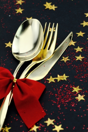 Christmas cutlery. Spoon, fork and knife stacked up on a starry background photo