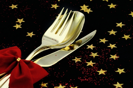 christmas catering: Christmas cutlery. Spoon, fork and knife stacked up on a starry background