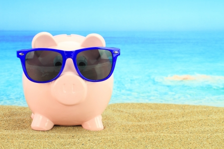 sales bank: Summer piggy bank with sunglasses on the beach