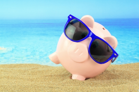 bank crisis: Summer piggy bank with sunglasses on the beach
