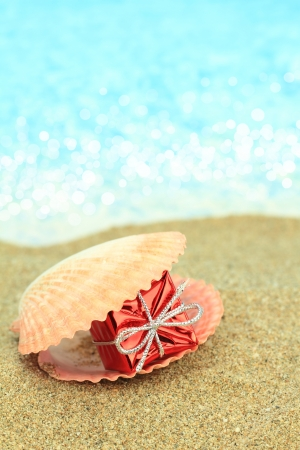 Gift box in a sea shell on the beach photo