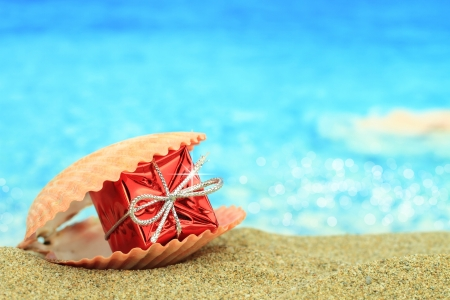 beach happy new year: Gift box in a sea shell on the beach Stock Photo