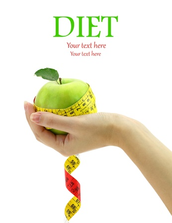 Diet concept. Female hand holding fresh apple with measuring tape photo