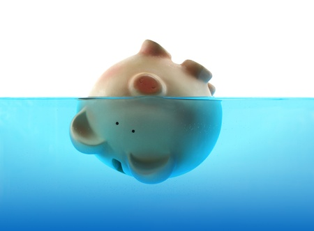 budget crisis: Drowning in debt represented by a piggy bank sinking in blue water