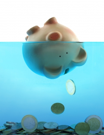 ahogarse: Ahogamiento en deuda representada por una hucha hundimiento en el agua azul Foto de archivo