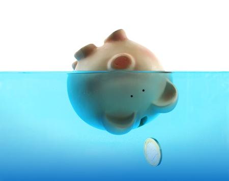 cuenta bancaria: Ahogamiento en deuda representada por una hucha hundimiento en el agua azul Foto de archivo