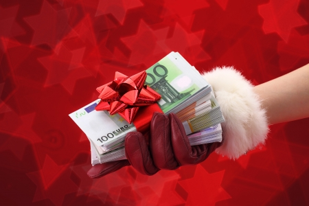 Womans hand with red glove holding gift of money  photo