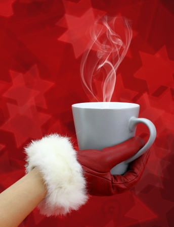 Womans hand with red glove holding a cup of coffee photo