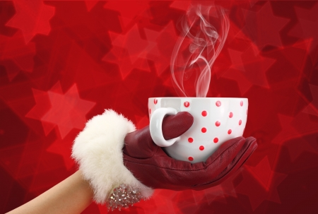 Womans hand with red glove holding a cup  photo