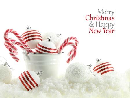 Bolas de Navidad y dulces en una taza en la nieve