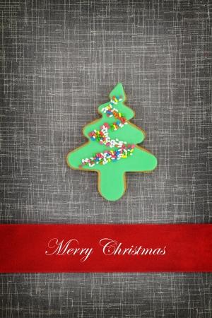 cioccolato natale: Cartolina di Natale con il biscotto albero su tessuto di fondo