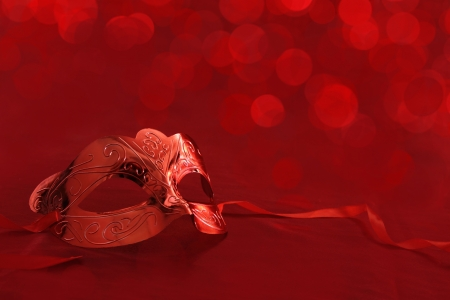 Vintage carnival mask in front of red lights background photo