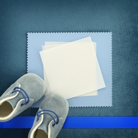 Blank card with baby shoes on blue background photo